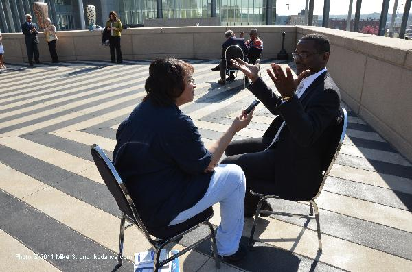 The Kansas City Call's Tracie Allen interviews Robert Battle on the terrace of Bartle Hall following the breakfast honoring Judith Jamison (in the background, being interviewed by Steve Paul of the KC Star) and Battle.