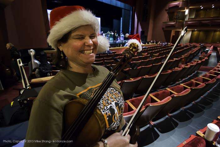Photo by Mike Strong (kcdance.com) - Violinist Richelle Basgall rehearsing in Santa hat with a tiny Santa hat on the carved head at the end of her violin