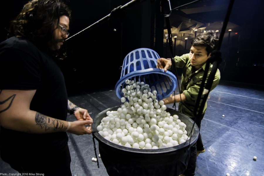 Cleaning up the balls after a performance. Cesar Kastro (right), property manager with Jonah Bokaer dumps a basket of balls into the large kettle used to drop the set of balls for the cascade.