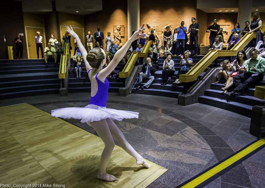 Young dancer with Cresendo Academy in an exhibition in the lobby of JCCC's Carlsen Center as a pre-show before New Dance Partners in theater behind them