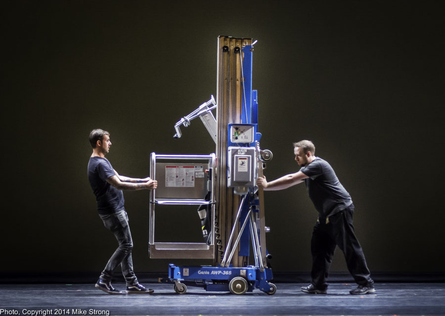 Stage crew moves a Genie lift
