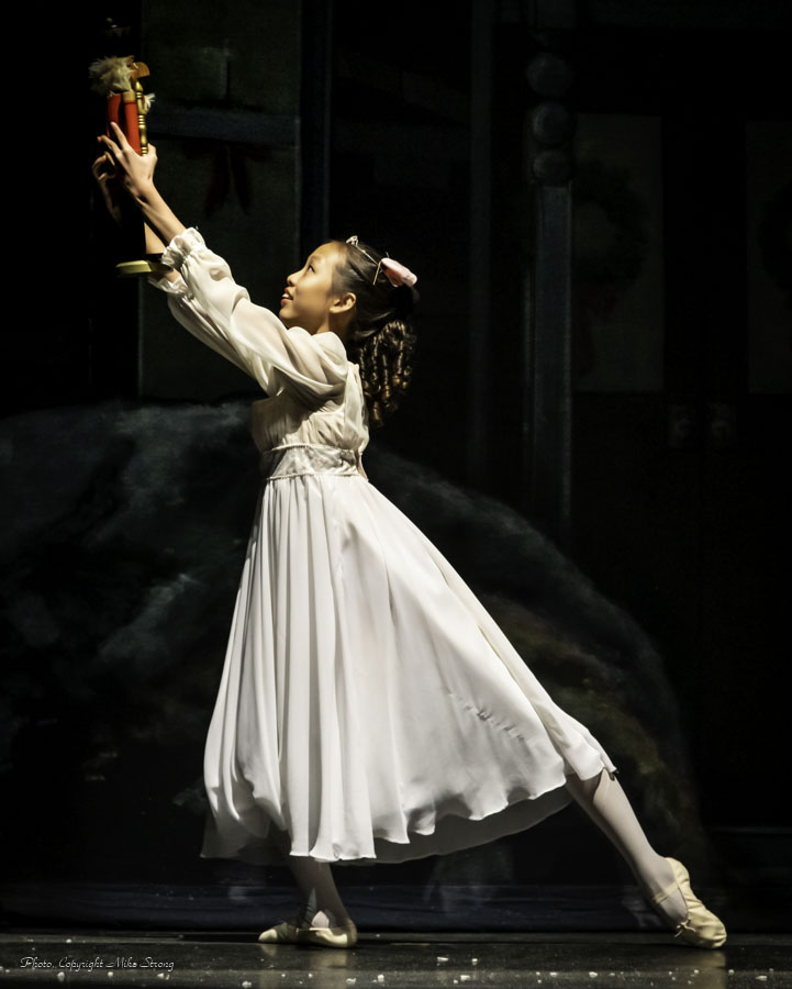 Arielle Li, as young Clara, hoisting the Nutcracker at the finale.