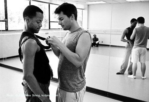 A persistent costume problem - Here choreographer Josh Beamish is adjusting Chris Barksdale's suspender which kept unsnapping in rehearsal - in UMKC annex studio room. - photo Mike Strong kcdance.com